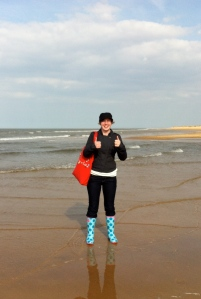 Me, on the beach, wearing wellies and making two 'thumbs up' signs